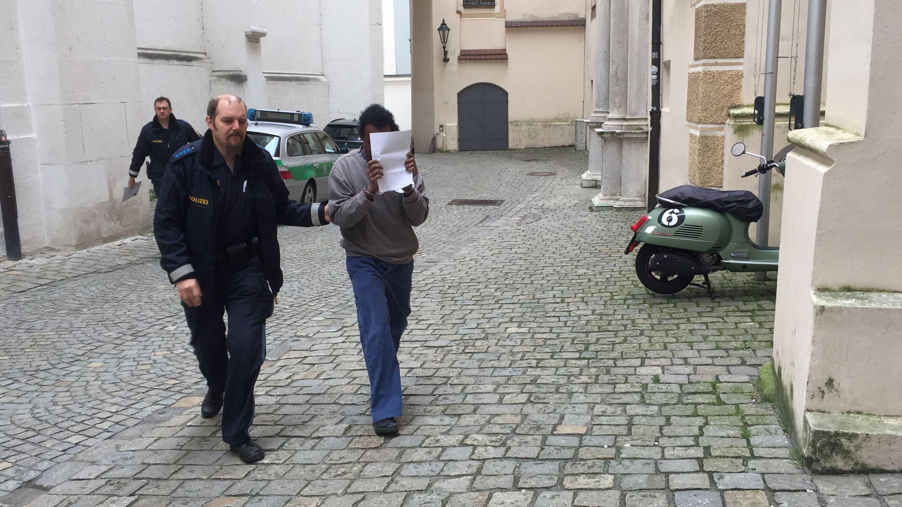 Der Angeklagte wird von der Polizei in das Gerichtsgebäude geführt