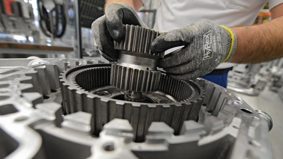 Ein Arbeiter baut in einem Werk ein Getriebe zusammen.