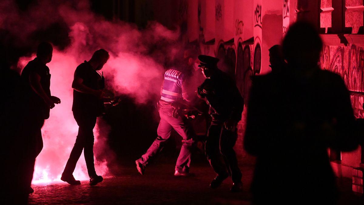 Polizisten laufen von der Stelle weg, an der zuvor bei einer Demonstration im Stadtteil Connewitz eine rote Pyro-Fackel explodiert war.