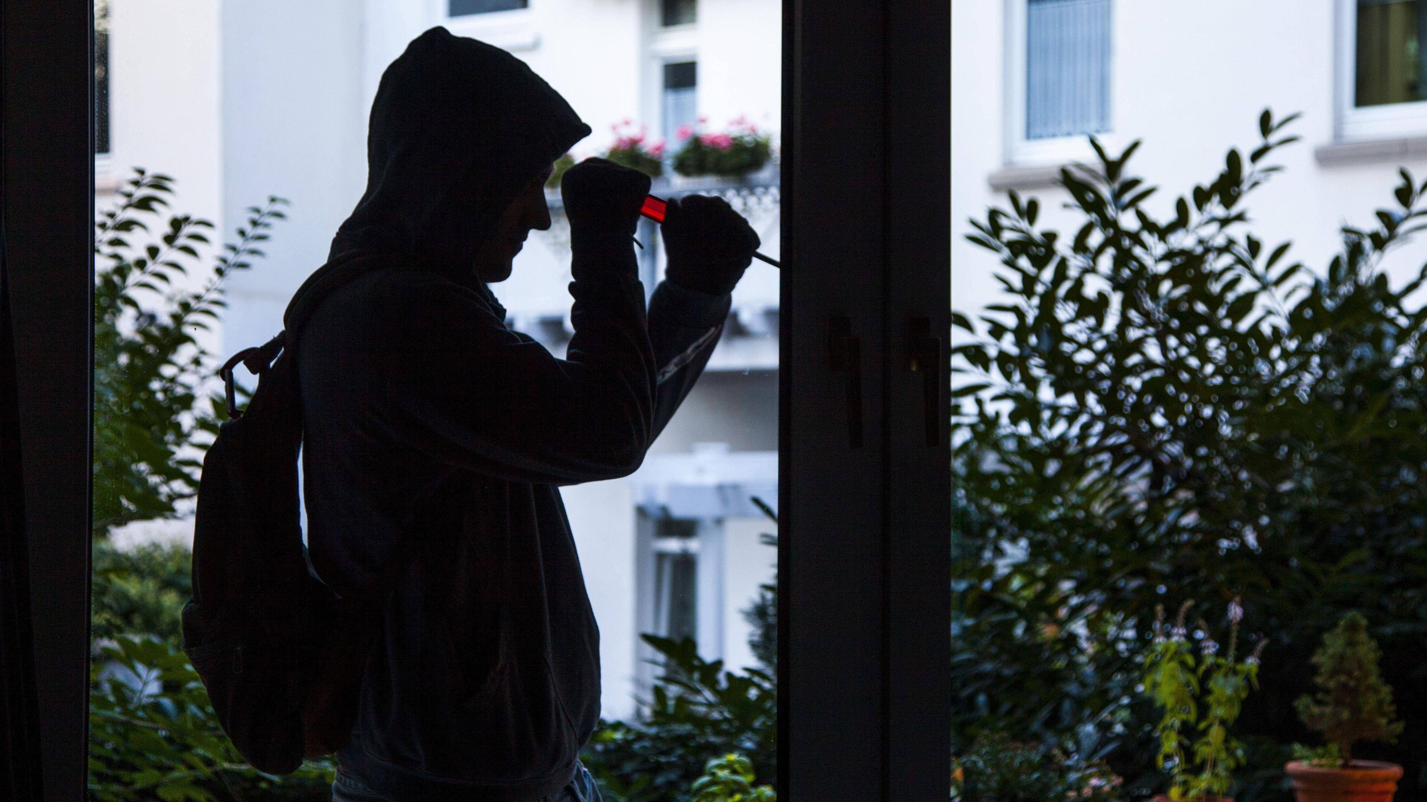 Einbrecher hebelt mit einem Schraubenzieher ein Fenster auf