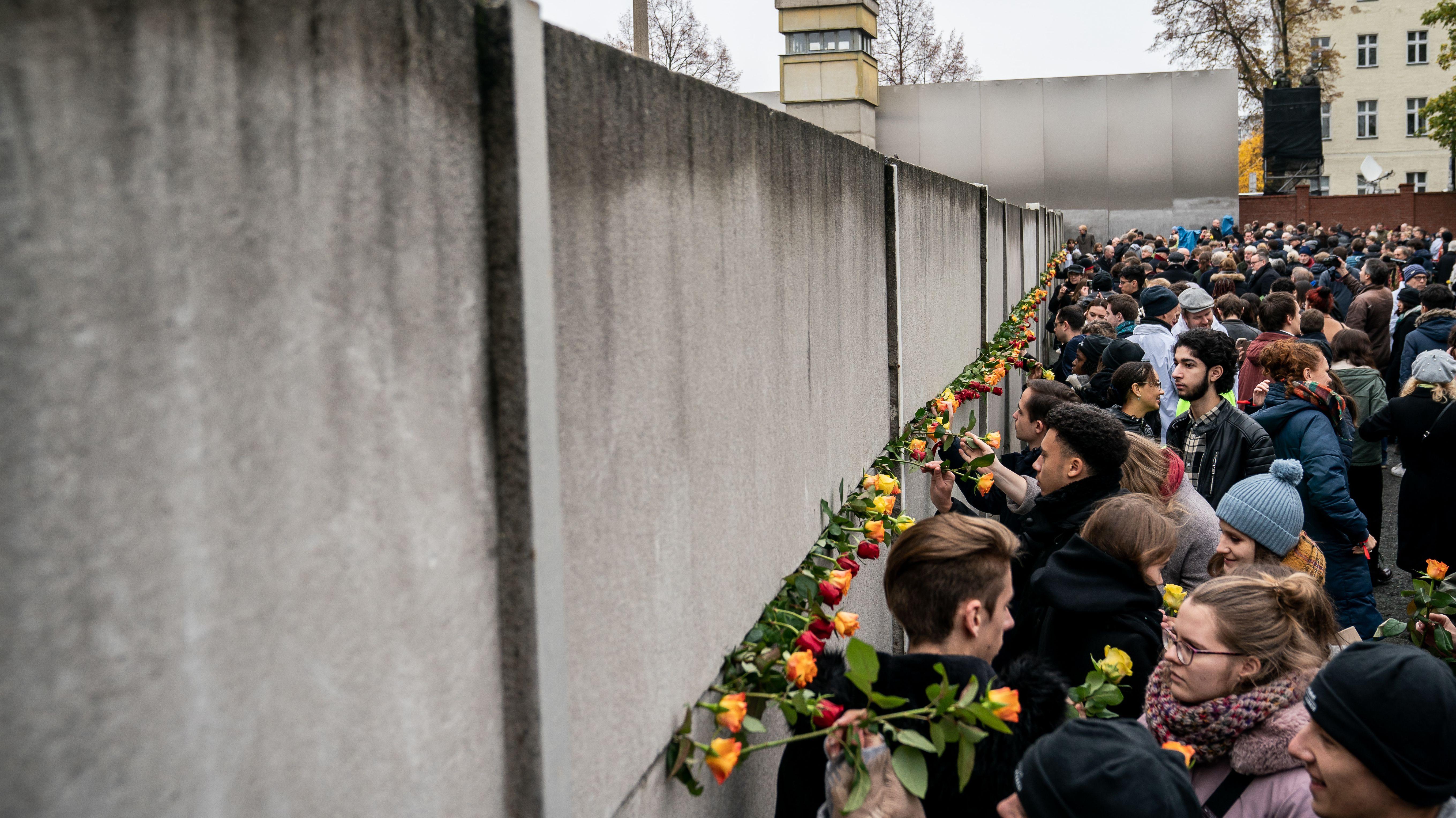 Zuvor haben die Menschen an einem anderen erhaltenen Mauerabschnitt an der Bernauer Straße Blumen das Betonmonstrum mit Blumen gefüttert.