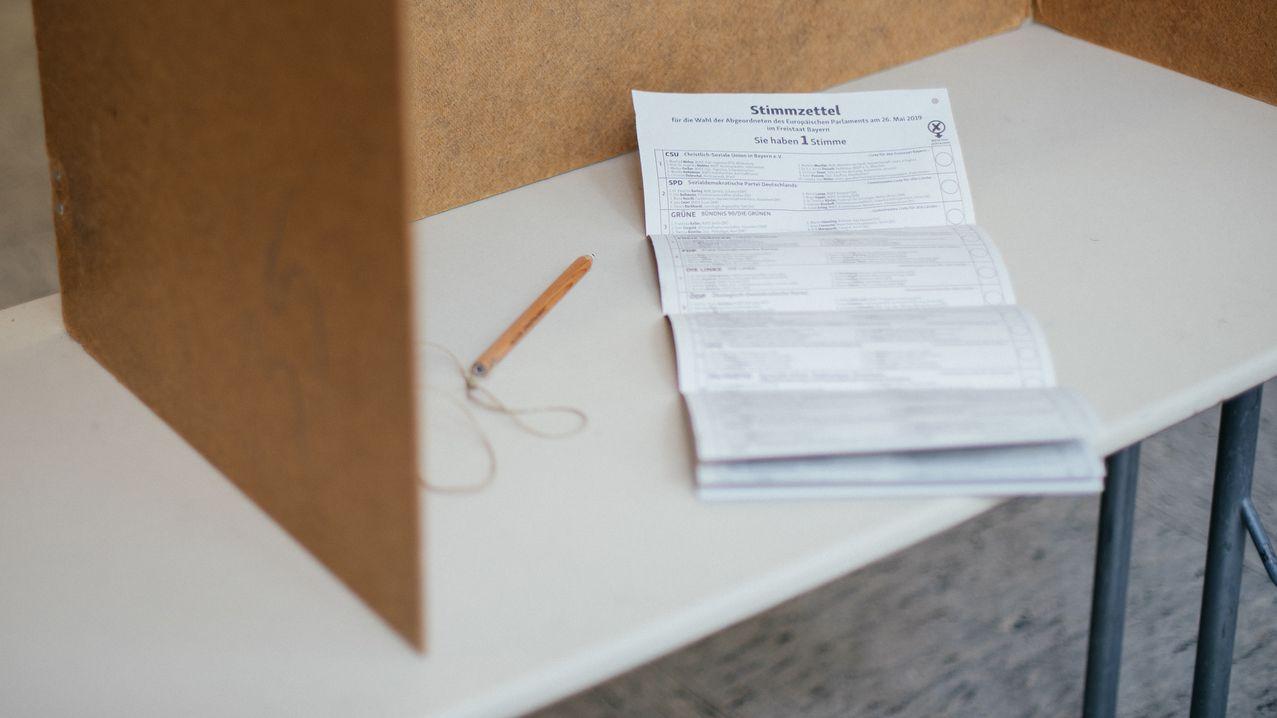 Symbolbild: Stimmzettel und Stift liegen in einer Wahlkabine