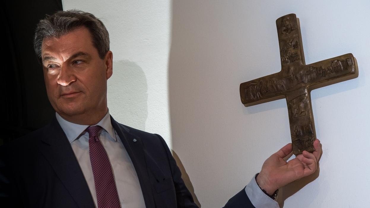Ministerpräsident Söder (CSU) hängt ein Kreuz im Eingangsbereich der bayerischen Staatskanzlei auf