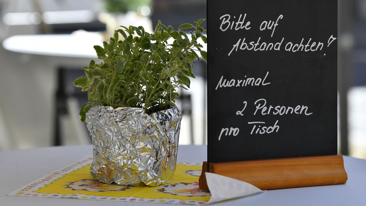 """""""Bitte auf Abstand achten! Maximal 2 Personen pro Tisch"""" steht auf einem Schild vor einem Lokal."""