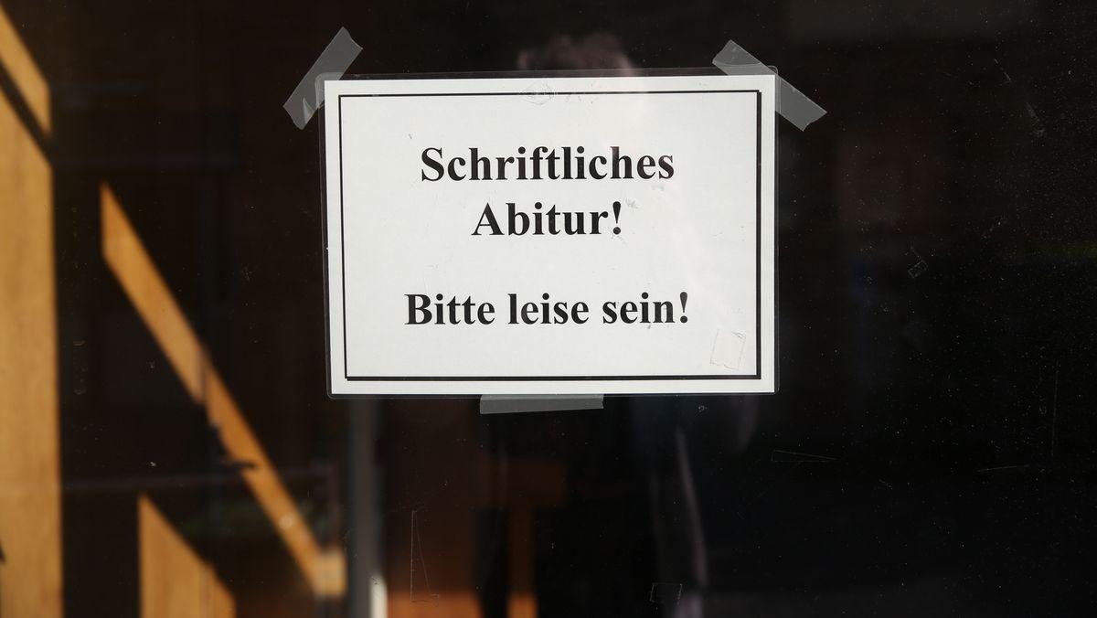 """Ein Papierschild mit der Aufschrift """"Schriftliches Abitur! Bitte leise sein!"""" hängt an der Tür eines Gymnasiums."""