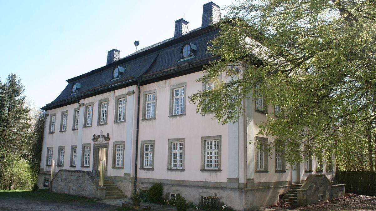 Das zweistöckige Schloss Erkersreuth hat einen schlichten Treppenaufgang, seitlich daneben Laubbäume.