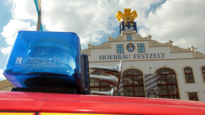 Symbolbild:  Einsatzfahrzeug und Blaulicht vor dem Hofbräu-Festzelt