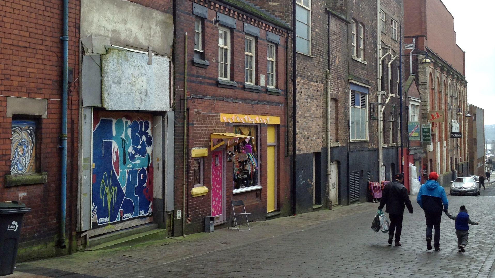 Ein Straße mit geschlossenen Geschäften und Graffiti, aufgenommen am 10.02.2017 in Stoke-on-Trent, England, Großbritannien.