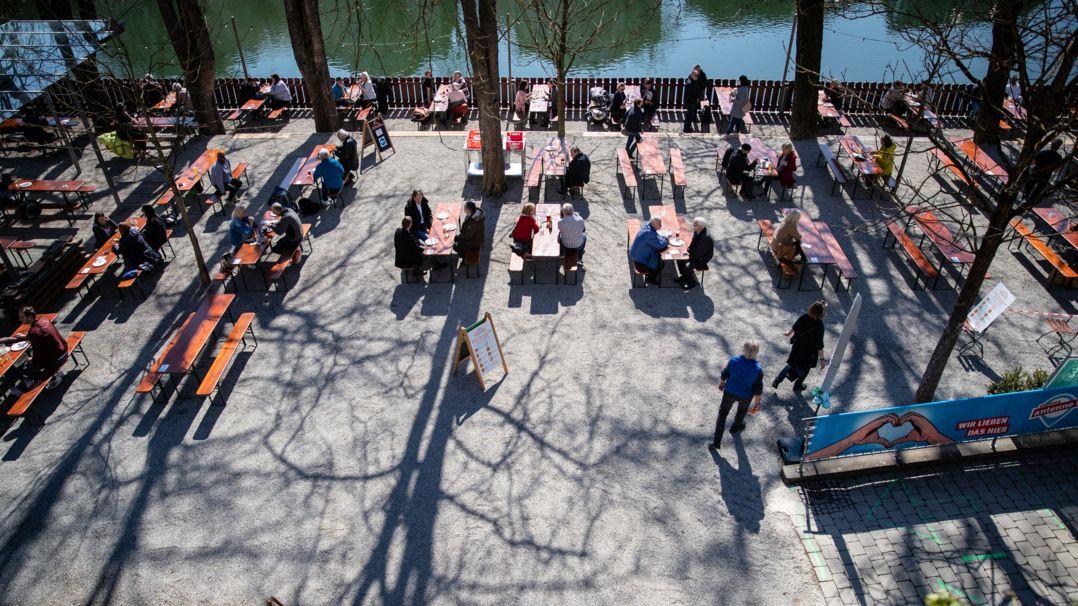 Gäste sitzen in einem Biergarten an weit auseinander stehenden Tischen