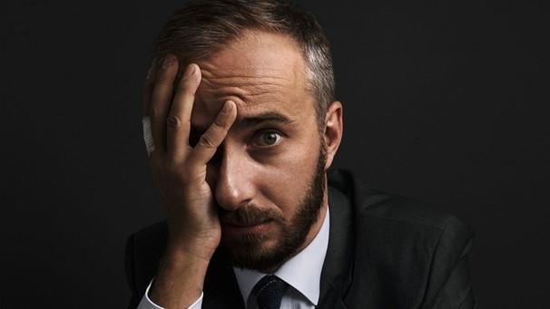 Ein Mann Ende dreißig im Anzug fasst sich ins Gesicht