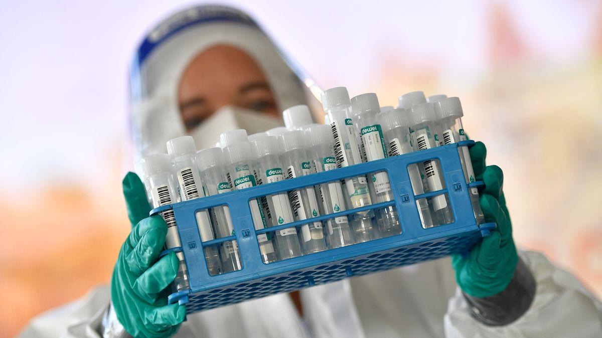 Medizinisches Personal trägt Teströhrchen mit Abstrichen von Testpersonen für Corona-Tests.