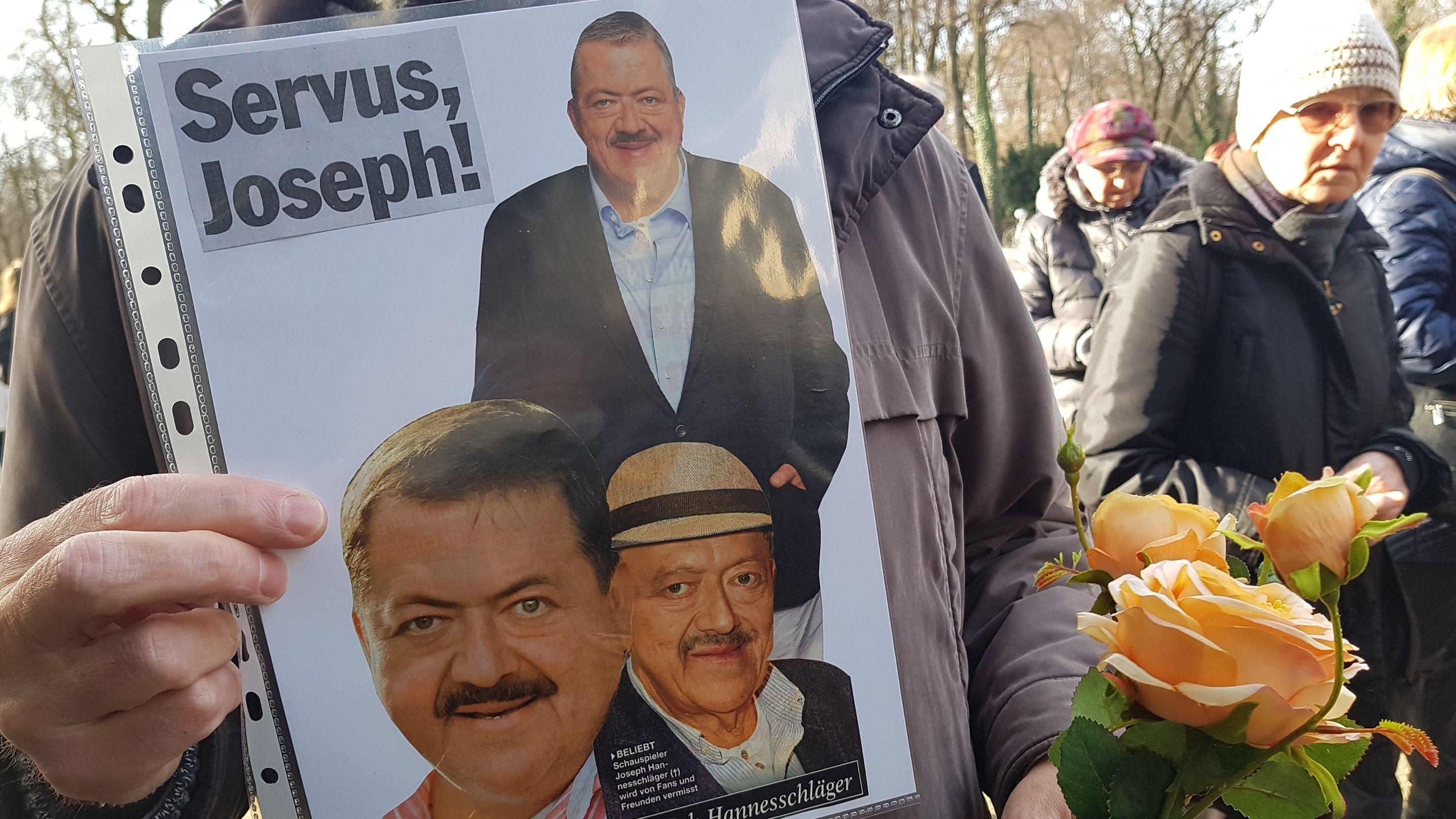 Ein Fan zeigt eine Folie mit ausgeschnittenen Bildern von Joseph Hannesschläger.