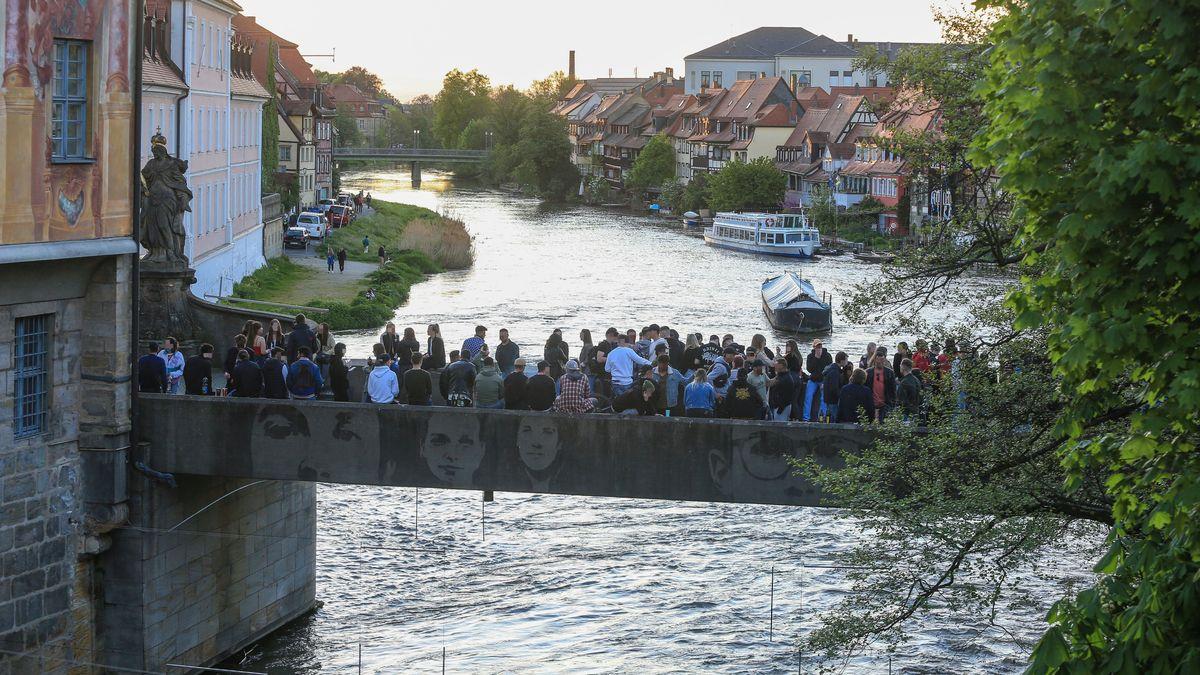 """Auf der """"Unteren Brücke"""" in Bamberg stehen viele Menschen ohne Maske nah beieinander."""