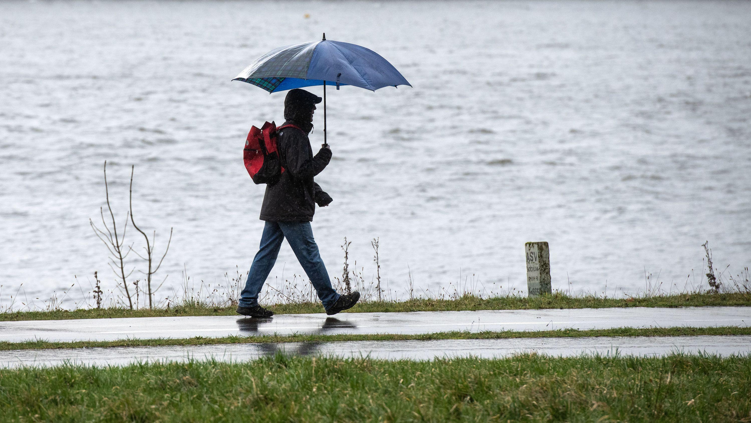 Ein Spaziergänger läuft mit einem Regenschirm an einen Fluss entlang.