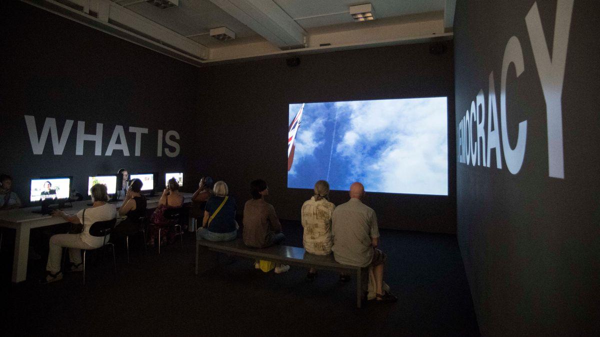 Videoinstallation von Oliver Ressler: Zuschauer sitzen vor Bildschirm