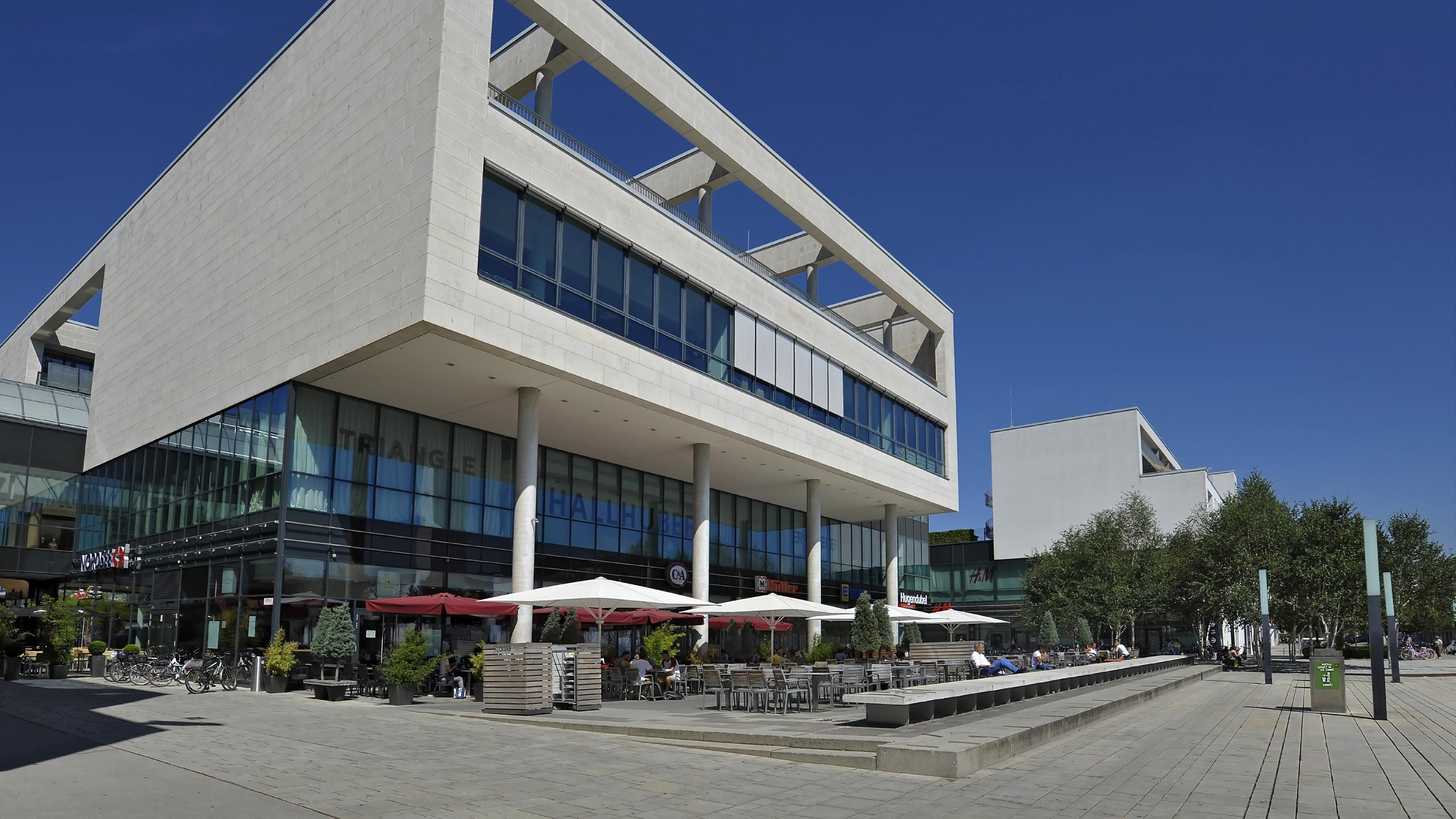 Die bestuhlte Terrasse einer Gaststätte vor dem Einkaufszentrum Messestadt West in München