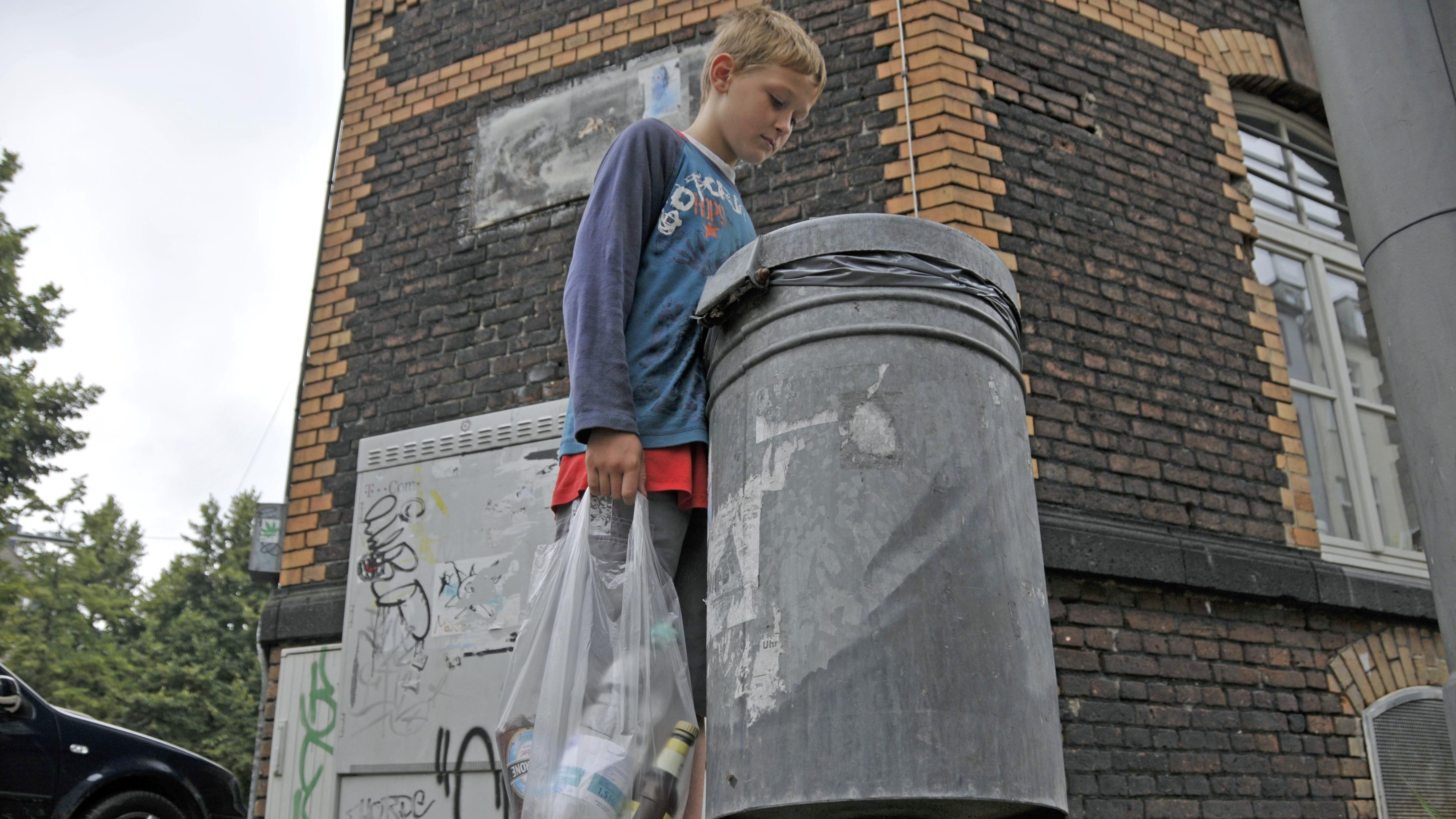 Ein neunjähriger Junge verdient sein Taschengeld durch Sammeln von Pfandflaschen