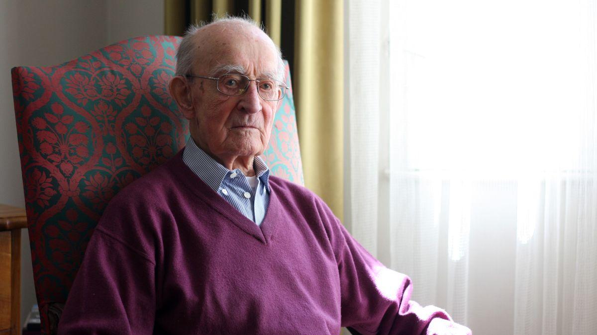 Norbert Kittel sitzt auf einem Stuhl in seinem Wohnzimmer.
