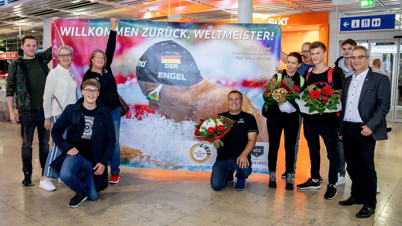 Taliso Engel (dritter von rechts) mit Unterstützern und Plakat am Flughafen