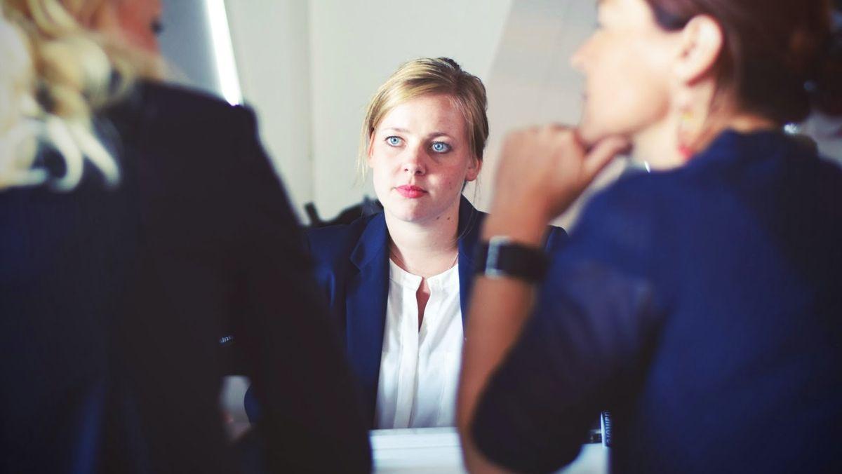 Eine junge Frau sitzt in einem Meeting Kolleginnen gegenüber