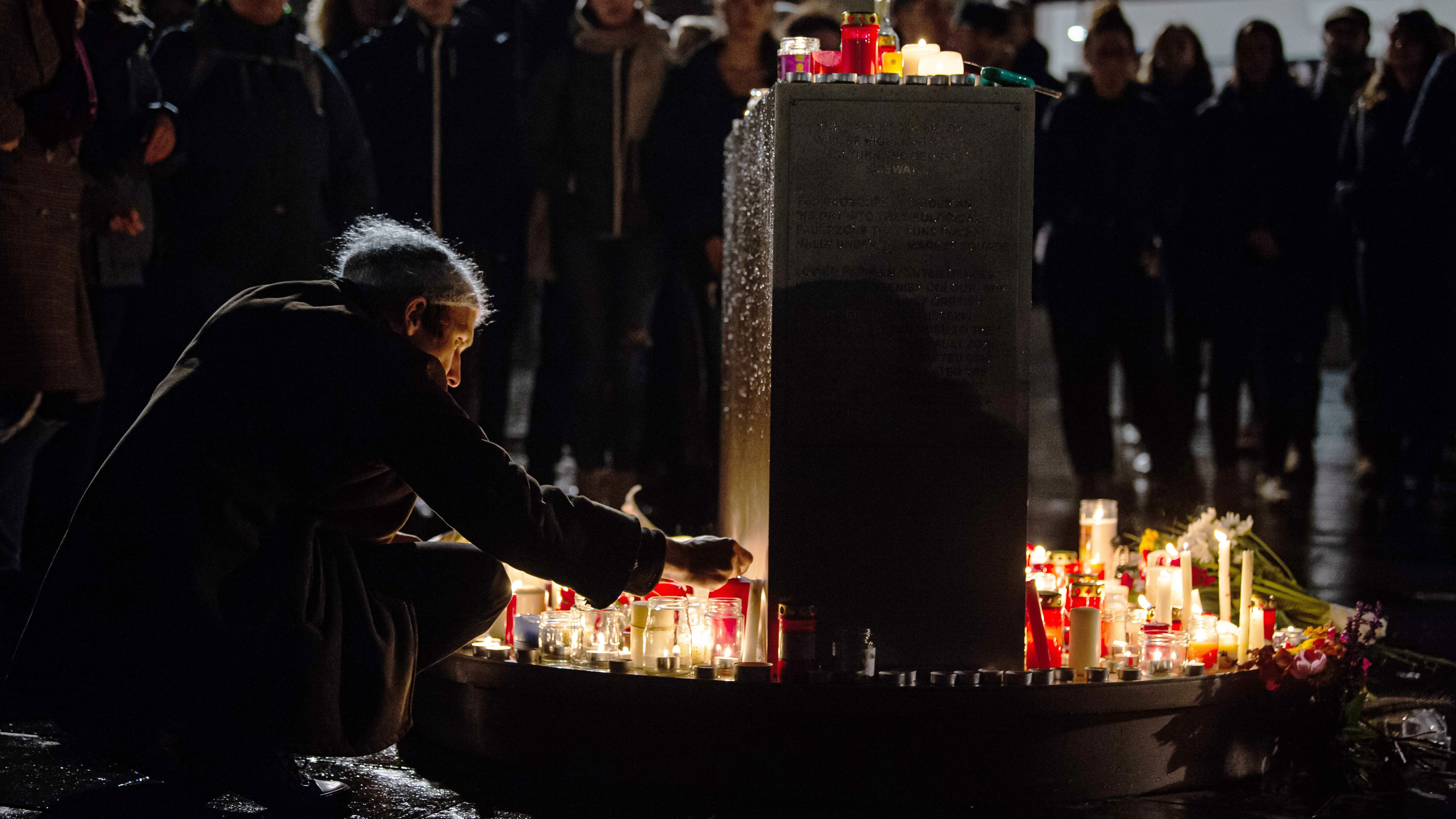 Marktplatz in Halle: Mann zündet eine Kerze an