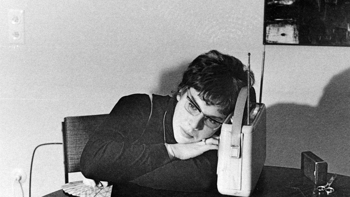 Ein Frau sitzt an einem Tisch und ist ganz nah an ihr Radio gerückt.