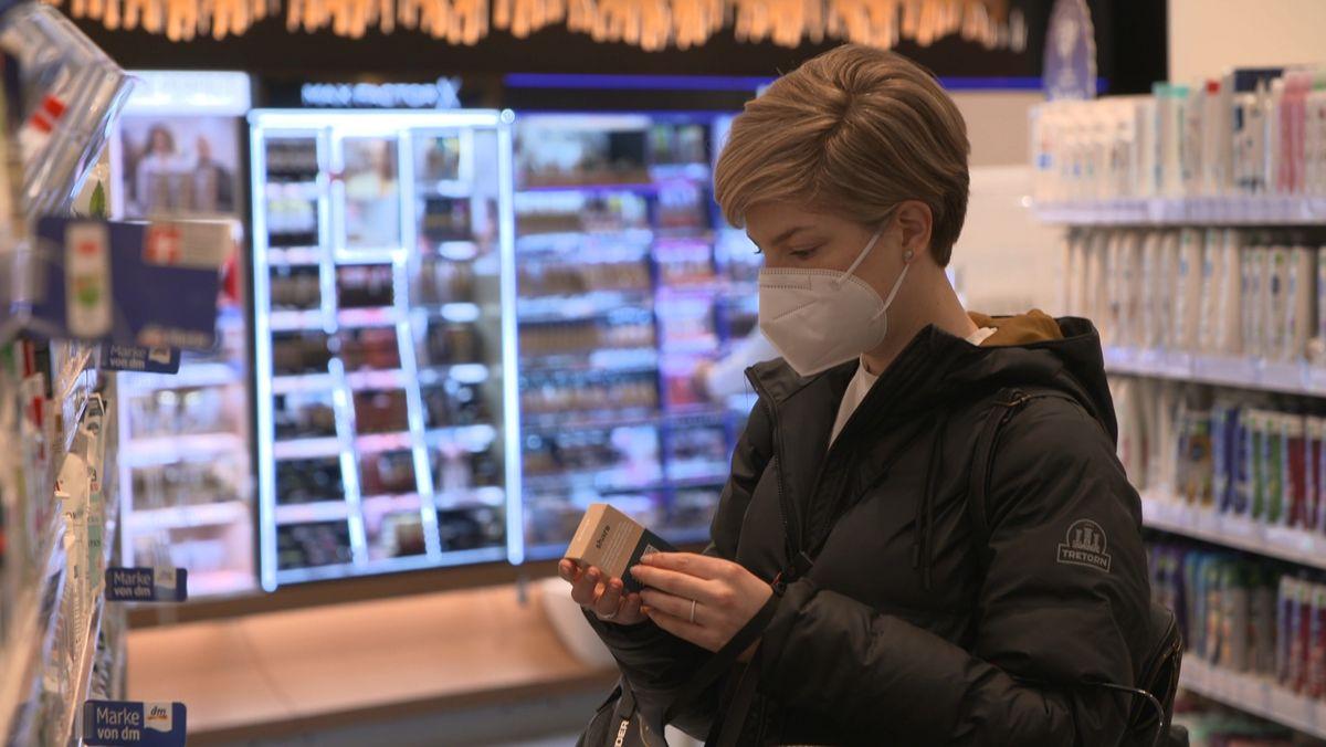Eine Frau beim Einkaufen überprüft die Inhaltsstoffe eines Produkts