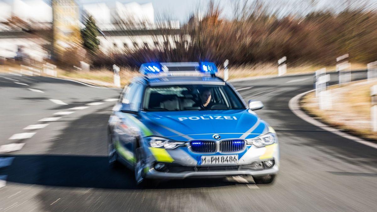 Ein Streifenwagen der Polizei fährt mit Blaulicht auf einer Straße
