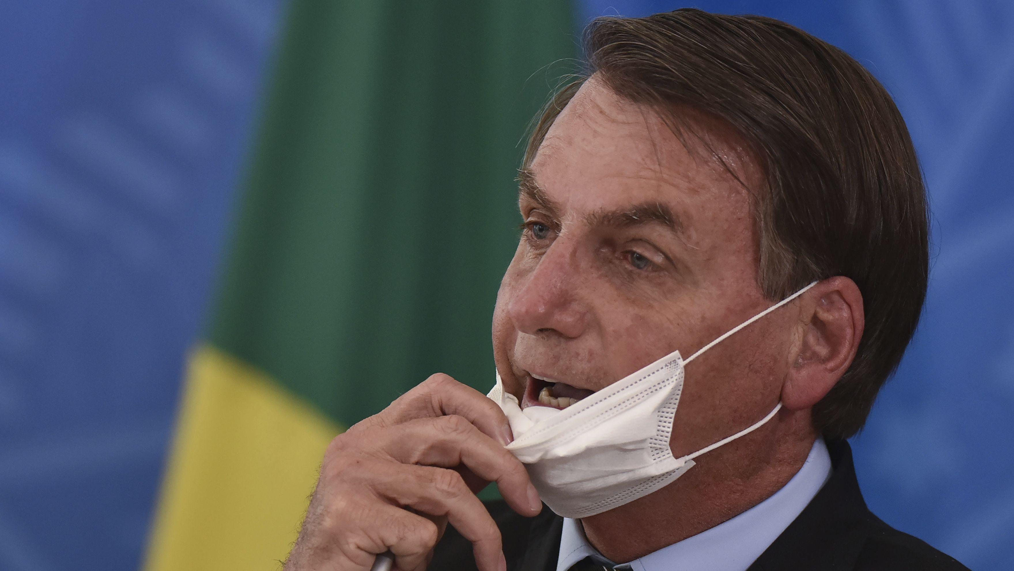 Brasiliens Präsident Jair Bolsonaro sieht in der Coronakrise nichts als Hysterie und Verschwörung. Hier nimmt er seinen Mundschutz ab, um mit Journalisten zu sprechen.