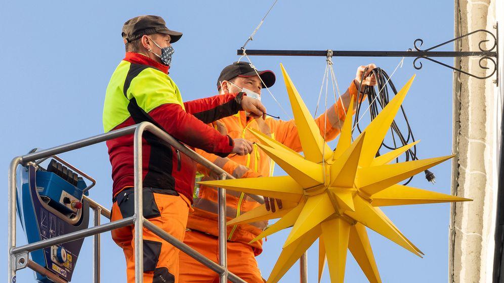 Arbeiter bringen am Rathaus von Hildburghausen einen Weihnachtsstern an | Bild:pa / dpa