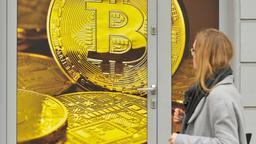 Eine Frau steht vor einer Tür voller Aufkleber symbolischer Bitcoins. | Bild:pa/dpa
