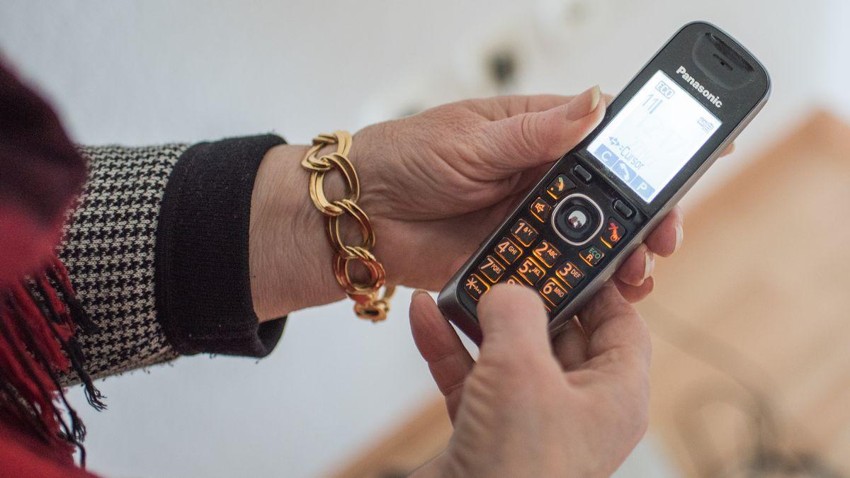 Ein Telefon in den Händen einer älteren Frau.