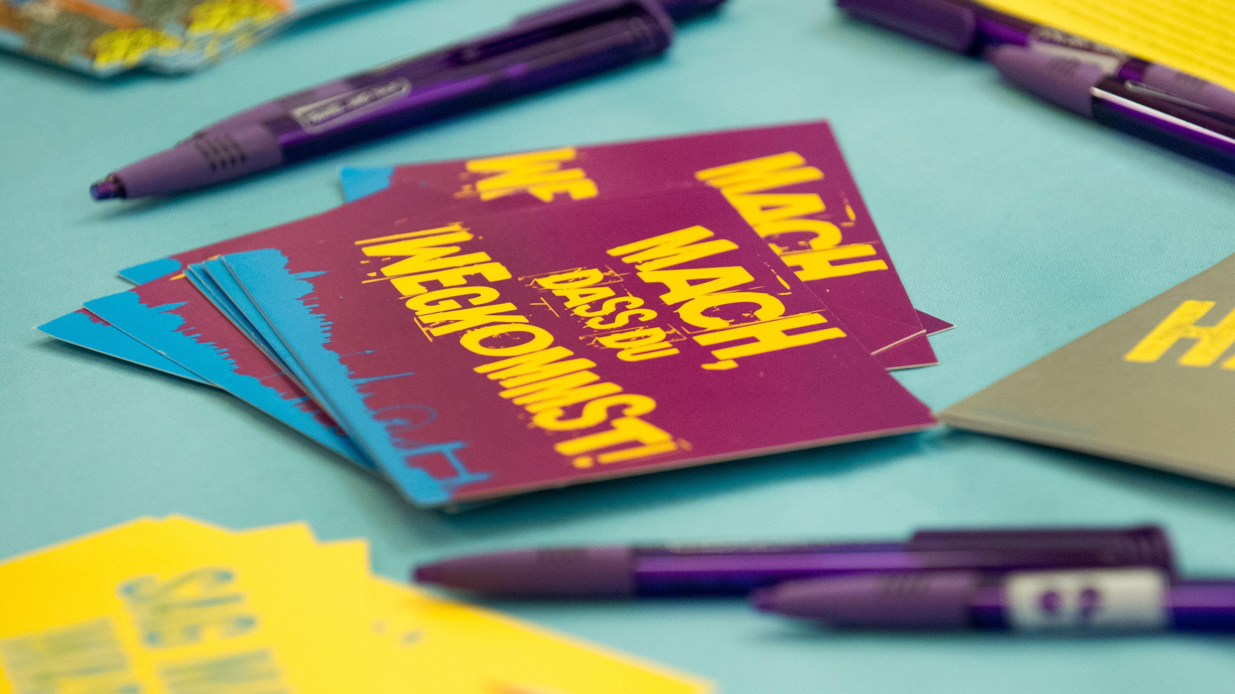 """Eine Postkarte mit der Aufschrift """"Mach, dass du wegkommst!"""" auf dem Tisch einer Schüler-Austausch-Messe"""
