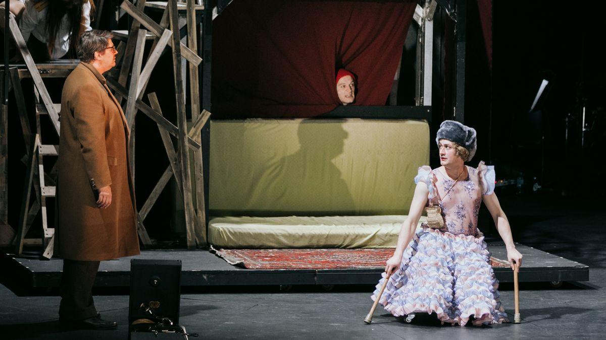 """Mann im Mantel steht einer Frau ohne Beine auf einem Rollbrett gegenüber, im Hintergrund ein Matratzenverschlag: """"Schwere Knochen"""" (Szenenfoto vom Wiener Volkstheater)"""