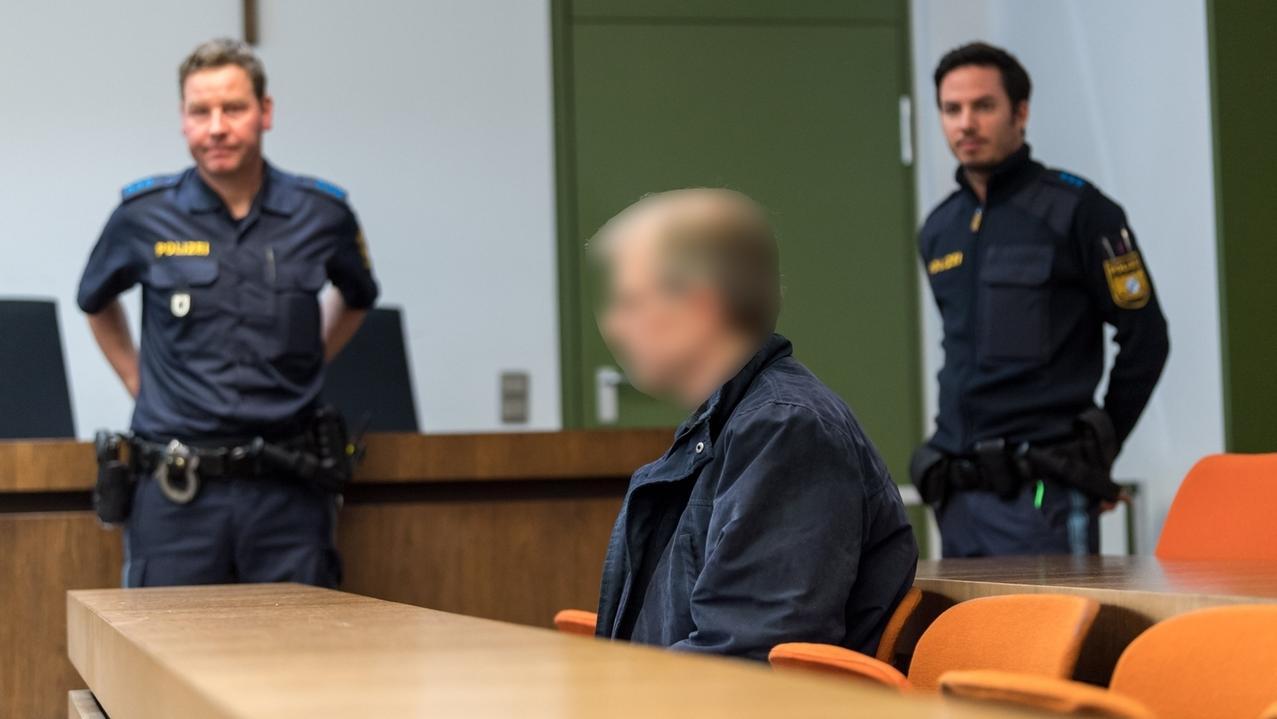 Der Angeklagte im Prozess des Doppelmords von Petershausen sitzt auf seinem Platz im Saal des Landgerichts München II und wird von zwei Polizeibeamten bewacht.