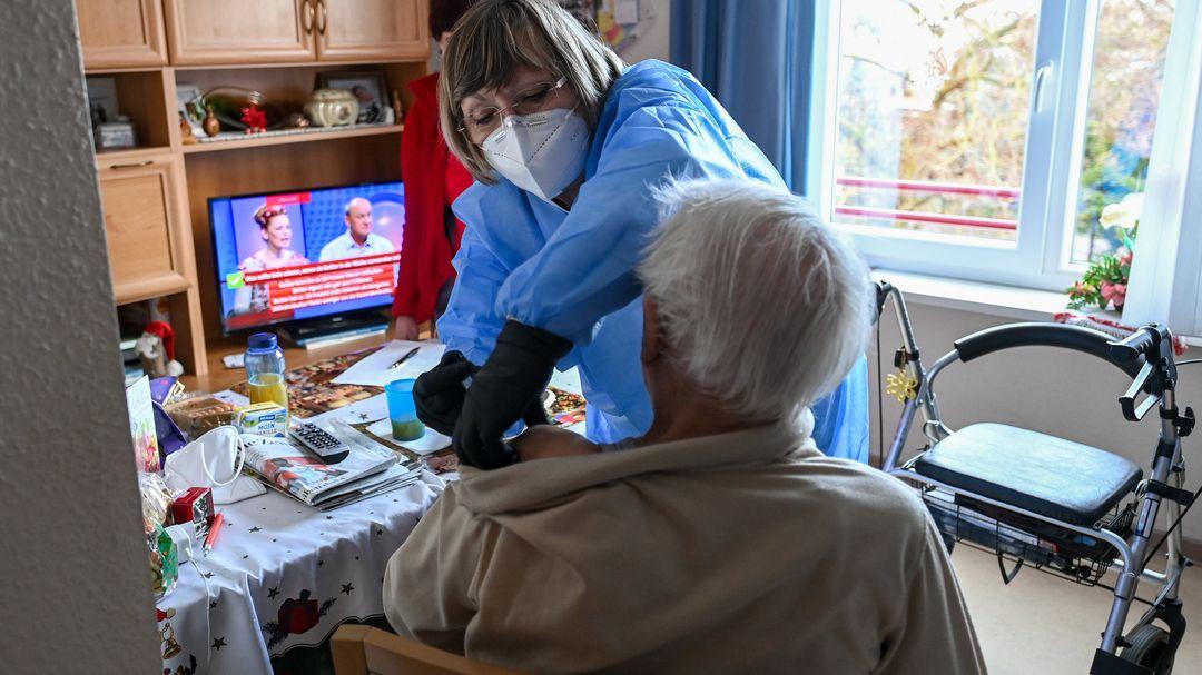 Ein Mann bekommt in einem Seniorenheim eine Impfung.