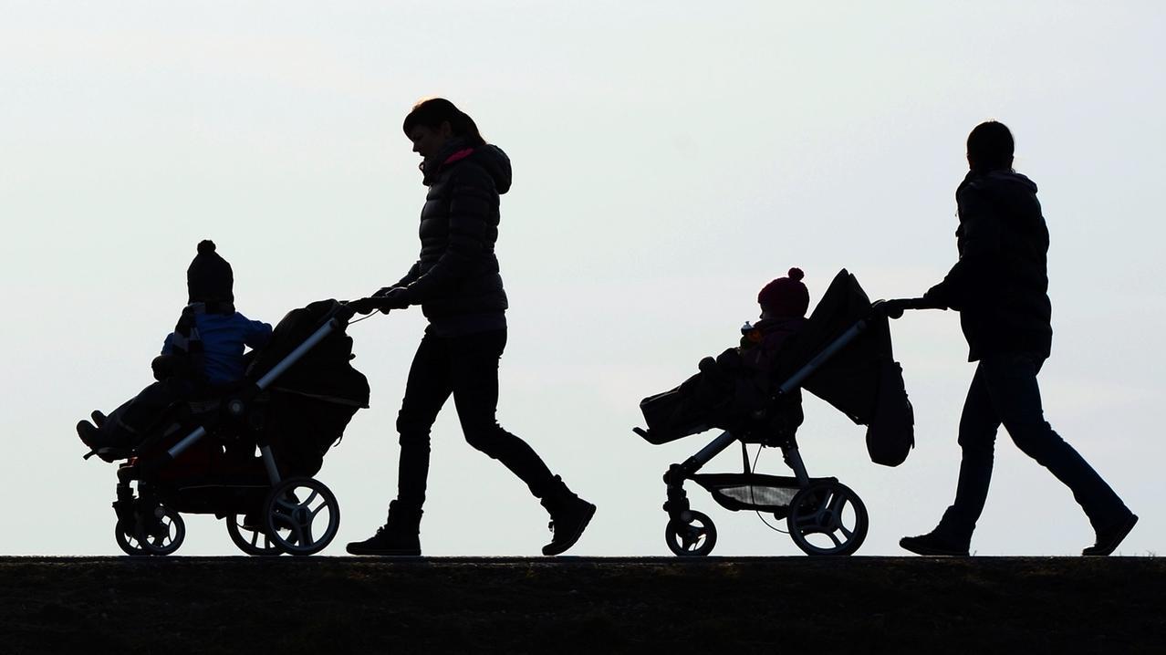 Eltern schieben zwei Kinder im Kinderwagen.