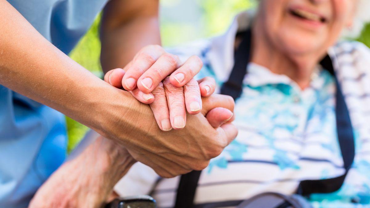 Ein Hand eines Pflegenden hält die Hand einer alten Frau.