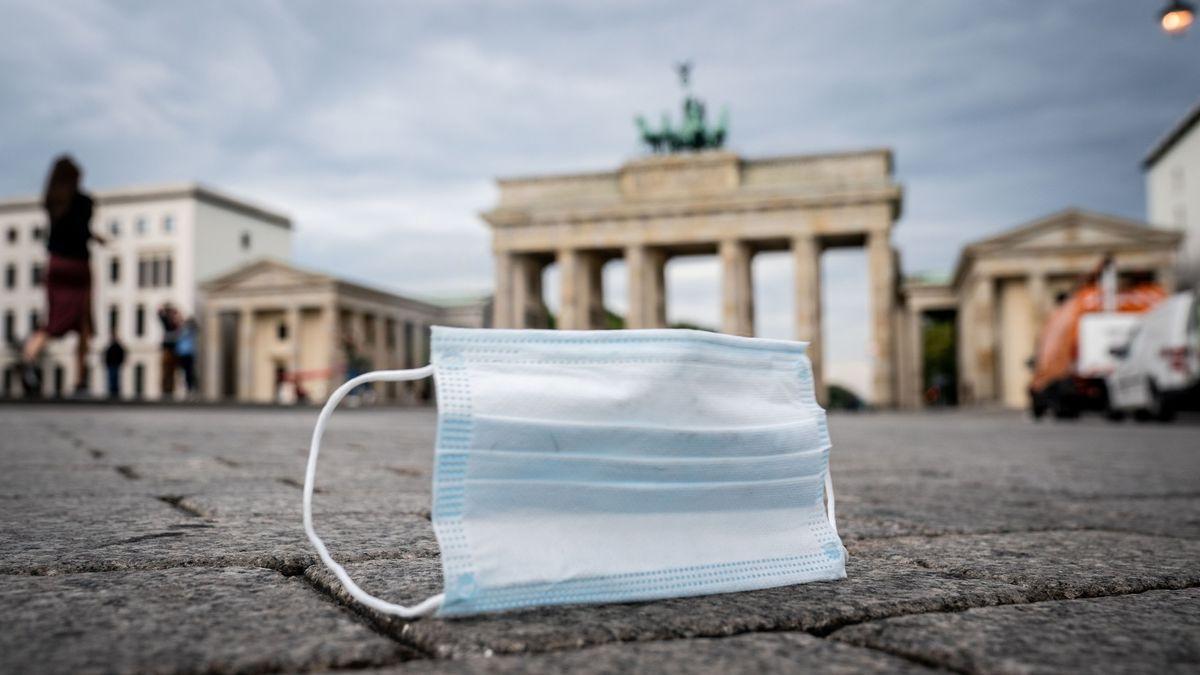 Ein Mund-Nasen-Schutz wird vom Wind über den Pariser Platz vor dem Brandenburger Tor geweht.
