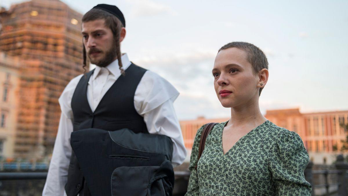 """Amit Rahav als Yanky Shapiro und Shira Haas als Esty spazieren in einer Szene der Serie """"Unorthodox"""" durch Berlin."""