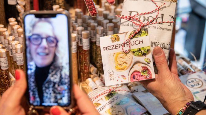 Per Videoanruf wird einer Kundin im Geschäft ein Rezeptbuch gezeigt (Symbolbild).