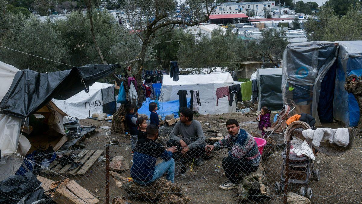Menschen sitzen im Flüchtlingslager Moria auf Lesbos am Boden