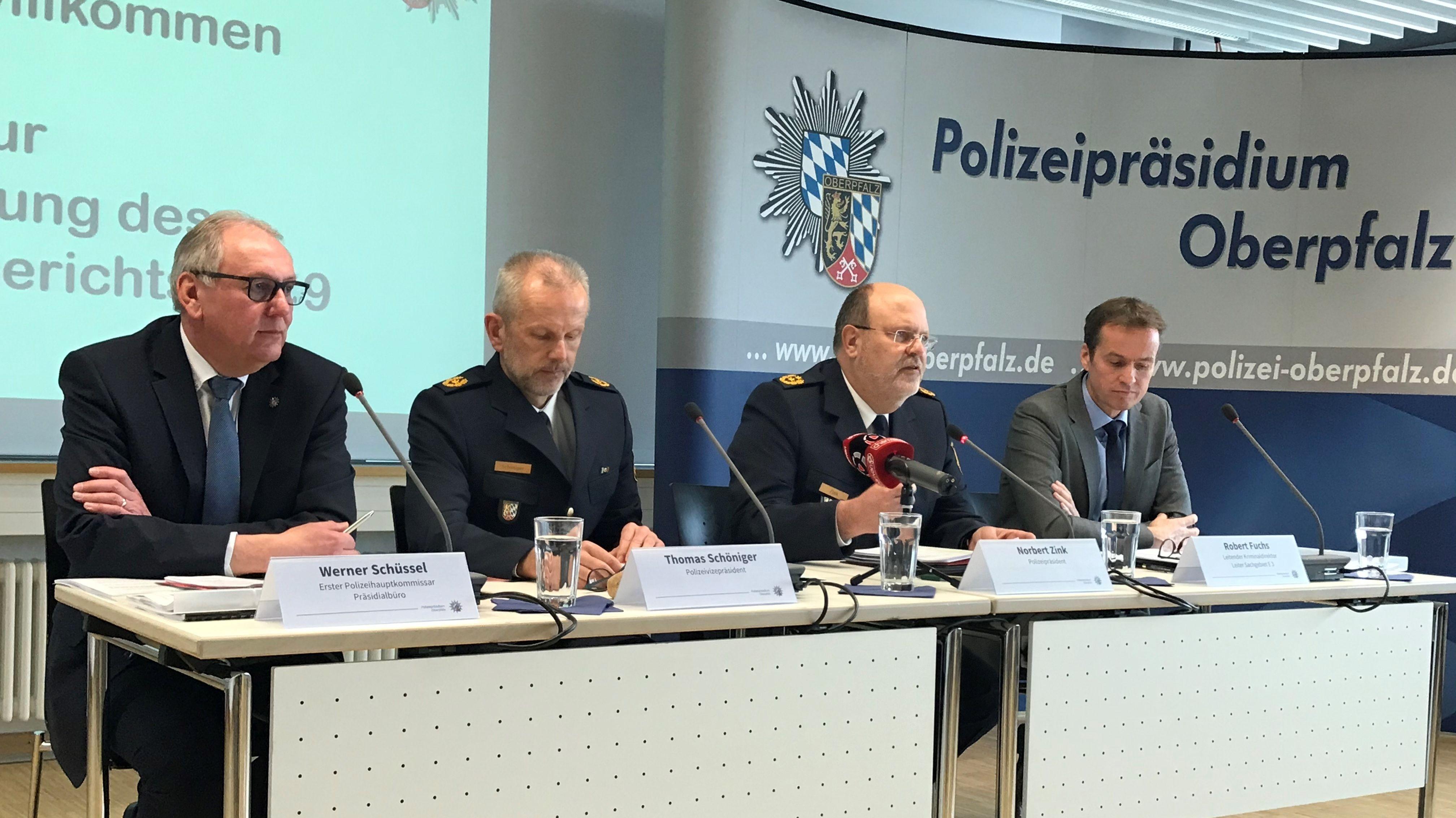 Vier Männer sitzen an einem Tisch vor Mikrofonen
