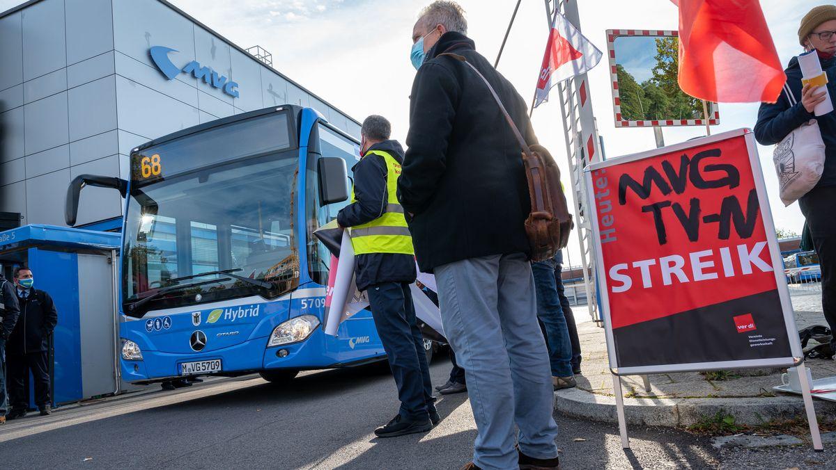 """09.10.2020, Bayern, München: Mitarbeiter der Münchner Verkehrsgesellschaft (MVG) stehen mit Plakaten vor einem Omnibusbahnhof neben einem Aufsteller mit der Aufschrift """"MVG TV-N Streik""""."""