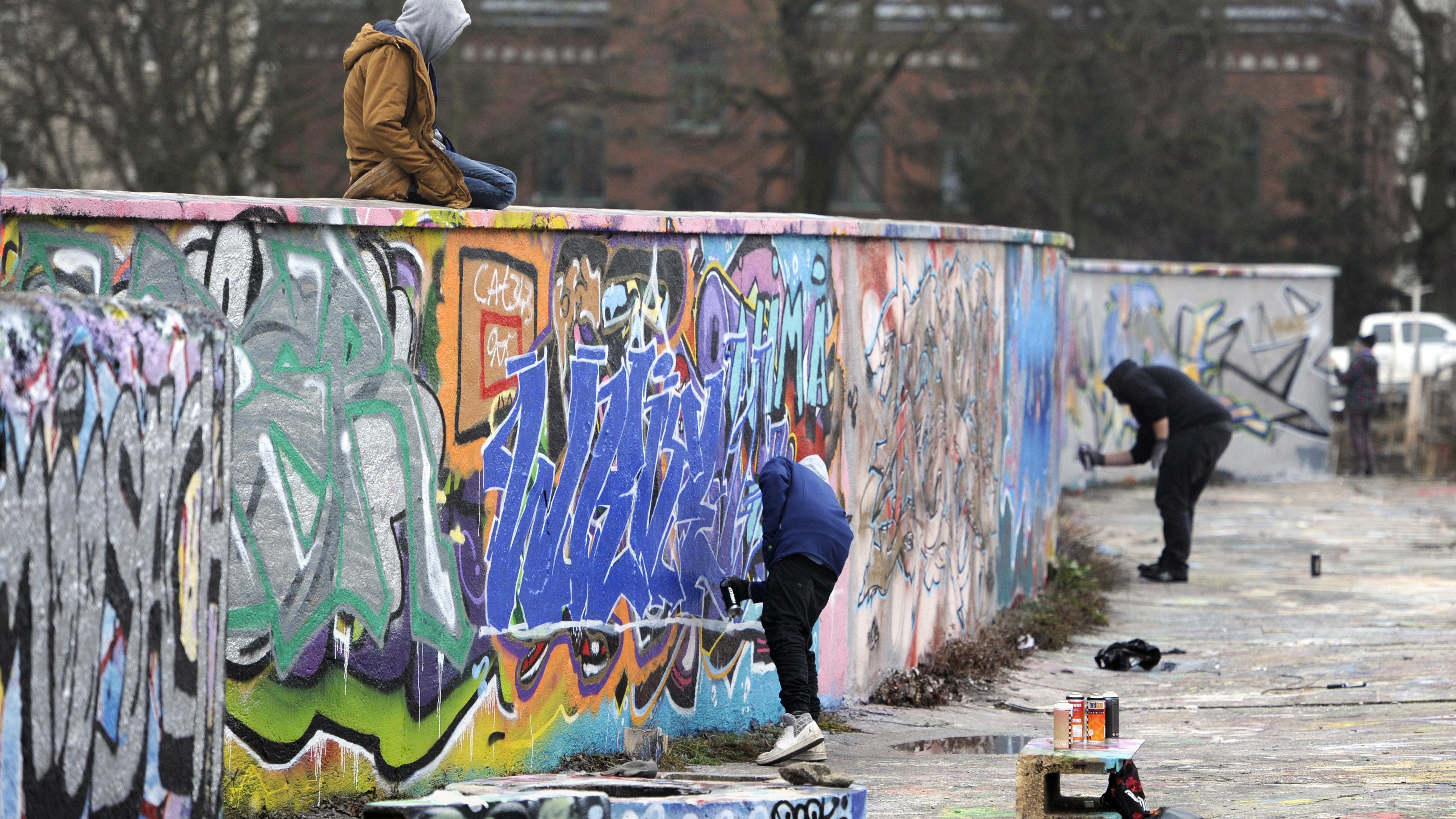 Graffiti-Sprayer besprayen eine Wand im Viehhof in München 2016