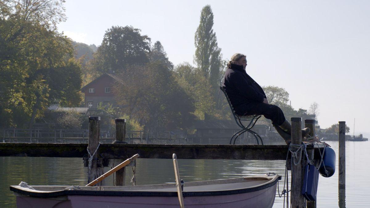 Mann sitzt auf dem Steg und blickt auf den Starnberger See.