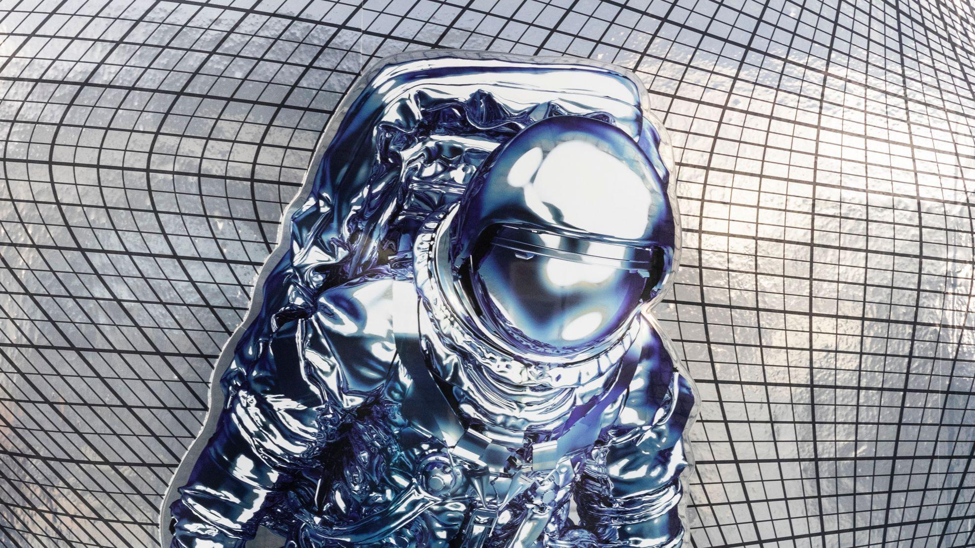 Ein Astronaut in silbernem Anzug schwebt durch einen Raum, der von einem Netzgitter umgeben ist.
