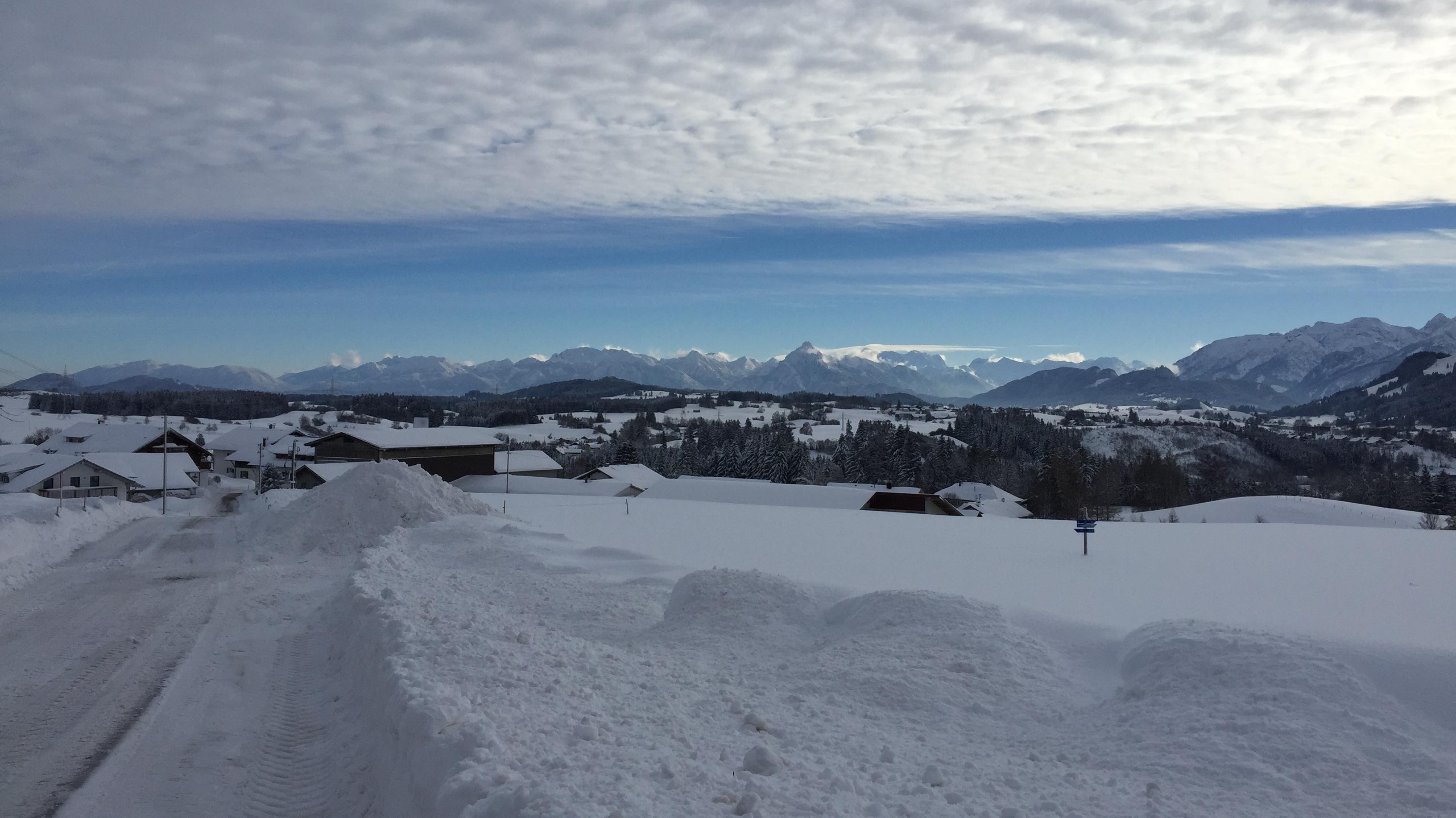 Blick von Schnakenhöhe über Maria Rain hinweg Richtung Osten, östliche Allgäuer Alpen, angrenzende Ammergauer Alpen bis Zugspitze. Wolkengrenze, nahender Schnee deutlich erkennbar