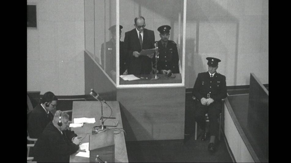 Adolf Eichmann im Glaskasten mit drei Polizisten, Verteidiger Dr. Robert Servatius und sein Assistent.