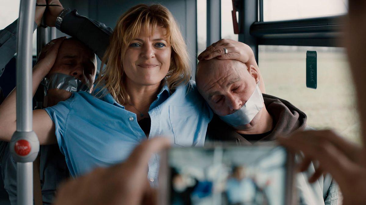 Blonde Frau posiert stolz  zwischen zwei gefesselten Menschen im Bus vor der Kamera